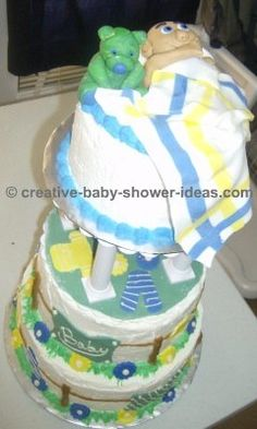 side of sleeping baby cake showing 3 tier cake on a cake stand and clothesline decoration on side