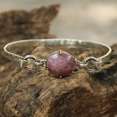 Pink sapphire bangle bracelet in textured silver with brass prong accents on the gemstone