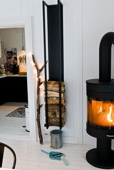 wood burner / fireplace and a really fabulous wood storage device hanging on the wall that is complete genius... Stacking the wood in a succinct pattern is quite beautiful as well as greatly functional...