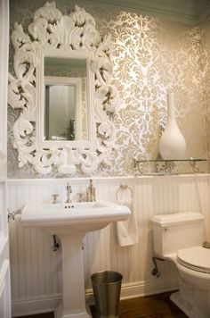 tunning powder room with white beadboard lower wall and golden metallic damask wallpapered upper wall. The bathroom features a traditional style pedestal sink paired with a ornate white Baroque mirror. Beside the sink hangs a nickel towel ring and nickel wastebasket. Over the toilet hangs a glass shelf holding a large white vase. decorpad.com