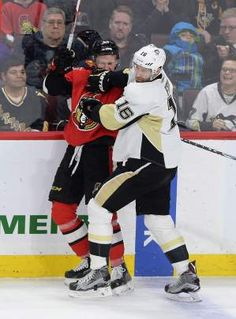 Penguins right wing Eric Fehr (right), hits Senators center Ryan Dzingel into the boards during the first period Tuesday.  — AP