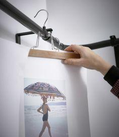 An interior designer hangs an IKEA BUMERANG pants hanger holding a piece of artwork from a rod.