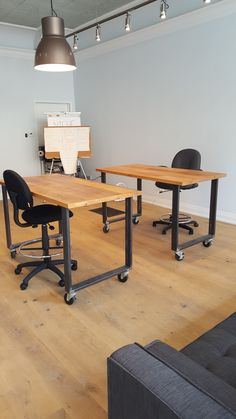 Custom office desks by barnboardstore.com - these are two desks made with reclaimed barn board tops mounted on industrial look raw steel legs. Locking wheels make the desks easily moved and held in place