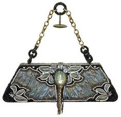 Mary Frances Fortune Teller Handbag has a bohemian and glamorous quality. The shimmering central motifs look like an art-nouveau dragonfly, while the organic motifs of beads and paillettes seem perfect for an Haute Couture gypsy. The inside of the purse is a beautiful brown and ivory floral silk . The frame and chain are an antiqued metal
