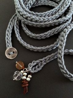 Light and soft crochet wrap bracelet or necklace made of cotton yarn in a perfect shade of light, silver gray featuring glass bead and leather cord charms. This fun and versatile accessory is approximately 54 (137.16) long and wraps about 7 times around a bionto.com