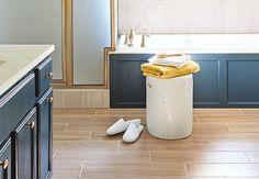 Light-tone planks of wood-look tile flooring in a bathroom.