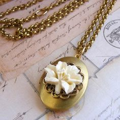 """Sweet and romantic, an oval locket has been embellished with brass filigree and a cream lily flower. Fill with a treasured photo to hold close to your heart. The locket hangs from a 26"""" brass rolo chain. The brass locket measures 1 1/4"""" x 7/8"""".All Out of the Blue jewelry includes free gift wrap"""