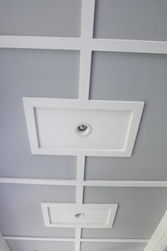 After adding fiberglass batting insulation to the ceiling, the couple covered it up with plywood and hid the seams with wood battens.