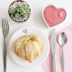 Mesa decorada em tons de rosa e branco. Prato branco com coração vazado e um croissant, potinho em formato de coração com brigadeiro com de rosa e uma suculenta.