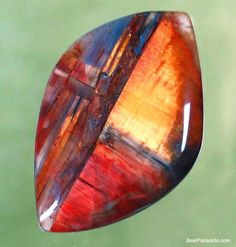 PIETERSITE cabochon - beautiful colors and nice design for an abstract. On left I see a blue and red door standing ajar, and beyond is a red floor, blue threshold, and sunlight streaming in the open doorway.