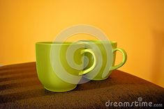 Two coffee cups on the chair with yellow wall background