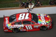 Kyle Busch, #18 Skittles Toyota, celebrates with the checkered flag after winning the NASCAR Sprint Cup Series Crown Royal Presents the Jeff Kyle 400 at the Brickyard at Indianapolis Motor Speedway on July 26, 2015 in Indianapolis, Indiana.