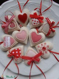 10 darab szívet varrtam tört fehér gyapjúfilcből,szalagokkal anyagdarabkákkal variáltam őket. Piros szalag akasztót kaptak. A szívek 6 cm magasak. Kézimunkával készültek,puha,hipoallergén anyaggal töltöttem őket. Kedves díszei lehetnek az Ünnepnek!