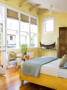 A mix of styles and cultures brings warmth and personality to this streamlined bedroom. The stage is set with pale yellow walls that complement the su. Light Yellow Bedrooms, Light Yellow Walls, Bedroom Yellow, Yellow Rooms, Yellow Light Shades, Light Blue, Wood Bedroom, Bedroom Decor, Bedroom Ideas