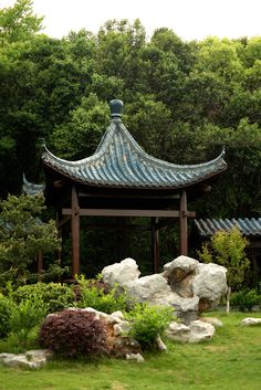 A pavillon of Chinese traditional style, in the garden, integrated with rockwork and plants.