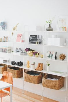 A connecting series of bookcases line the wall, providing a customizable amount of storage. Woven baskets tucked into the bottom shelf are perfect for organizing mail and other work-related clutter, while the upper shelves provide a display area for objet d'art, such as a gold urchin.  Photo by Claire Esparros via Style Me Pretty
