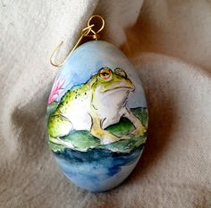 A sleepy bullfrog, resting on a lily pad on a sunny summer day, hand painted on a real, blown goose egg. This original painting is comprised
