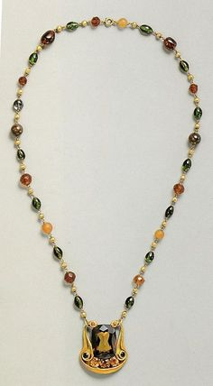 Alexandrite Necklace, L.C. Tiffany, 1914-15. Alexandrite, semi-precious stones, gold. Tiffany greatly admired the Alexandrite and kept in his own collection until gifting it to his companion Sarah Hanley. Here, the center stone is set into a restrained art nouveau mount, with beaded chain of gold, amber, carnelian, garnet, opal, orange and blue sapphire, and tourmaline.