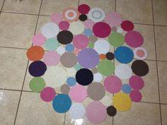 Tapete redondo confeccionado em barbante com círculos de diversas cores....