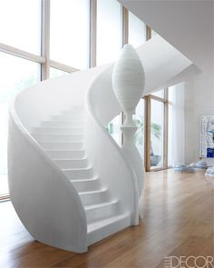 In this entry, the plaster staircase and the sculpture are custom designs, and the floors are walnut.