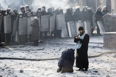 A man kneels before an Orthodox priest in an area separating police and anti-government protesters near Dynamo Stadium on Jan. 25, 2014, in Kiev. (Rob Stothard/Getty Images)