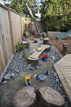A Dry river bed instead of a traditional sand pit. Large and smaller river rock lining a sand river with tree stumps, ferns and toys                                                                                                                                                                                 More