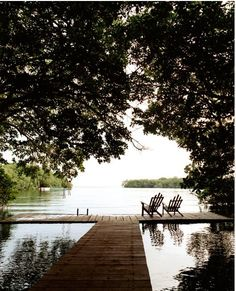 Adirondack chairs sitting on a simple deck on the river. Definitely could handle living here.