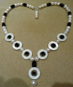 Made with Pearls, black beads and shell circles.