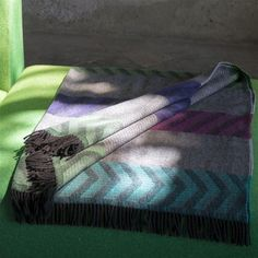Tranquil granite grey tones are offset with vibrant sections of graphic chevrons and stripes in shades of purple and green. Wool with a wonderful sensual mohair mix, and finishing to fringes at either end.