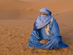 """The Tuareg people are predominantly nomadic people of the sahara desert, mostly in the Northern reaches of Mali near Timbuktu and Kidal but are also indigenous to Morocco. They are often referred to as """"Blue Men of the desert"""" – because their robes are dyed indigo blue. They traditionally live in small tribes with between 30 and 100 family members and keep camels, goats, cattle and chicken which graze the land."""