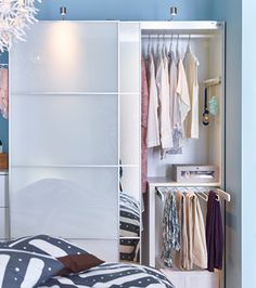 A white wardrobe filled with clothes
