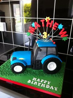 Shaped blue tractor cake, made for a little boys third birthday. Tractor wheels made out of Rice Krispies and marshmallows and covered in black fondant.