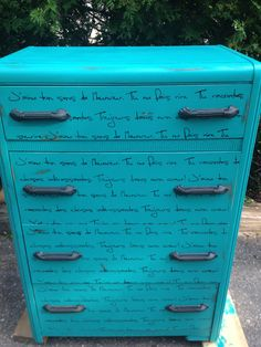 teal dresser with black script writing