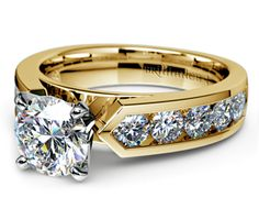 Ten round cut diamonds are channel set in this yellow gold diamond engagement ring setting, accenting your choice of center diamond. 1 carat total diamond weight.