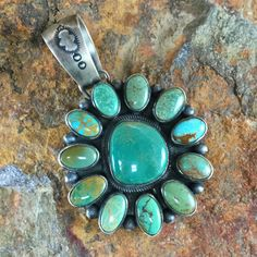 This beautiful Sterling Silver Pendant features a large centerstone of Fox Turquoise surrounded by 11 small Fox Turquoise stones. Fox Turquoise is mined in northeast Nevada. Crafted by Native American