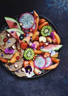 Fruit platter with pancakes, kiwi, pitaya, watermelon, apricots and edible blossoms