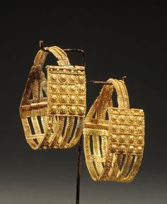 ETRUSCAN GOLD FILIGREE EARRINGS Openwork ribbons filled with wire bands, bosses, scrolls. Probably from Vetulonia Ca. 1st 1/4 of the 7th Century BC.