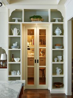 Small sliding doors that open in middle for area next to refrigerator takes up less space in wall on both sides than a barn door or pocket door