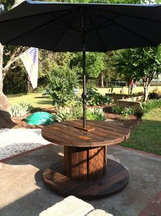 "Spool table stained and umbrella added. Used plywood block in ctr of table top and bottom to make hole the perfect fit for the umbrella. Added 4 2x4 blocks on the bottom as ""feet"" to level it."