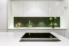 Olive green glass splashback against a white high gloss modern kitchen.