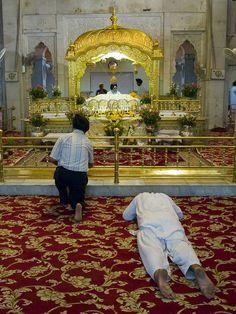 Sikh devotee bows toward Shiri Guru Granth Sahib to receive blessings.
