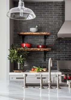 This stylish kitchen features a gray subway tile backsplash paired with white and gray marble countertops. Brushed nickel fixtures line the kitchen island sink, while a glass pendant light hangs above. Built-in wooden shelves provide the perfect spot for displaying bold red cookware.