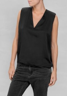 A relaxed-fit top made from a satin fabric with subtle sheen. Featuring a flattering V-neck and padded shoulders for added structure.