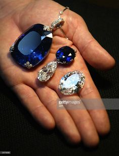 A man holds a 478 carat sapphire (L) which was previously owned by Queen Marie of Romania,   AFP PHOTO/Jim WATSON  (Photo credit should read JIM WATSON/AFP/Getty Images)