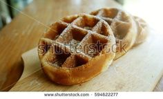 Belgian waffles with icing sugar. Popular snacks to eat with coffee. Made from flour, milk, butter, eggs, sugar. Highly calorie bakery. The light from the window. Vintage style.