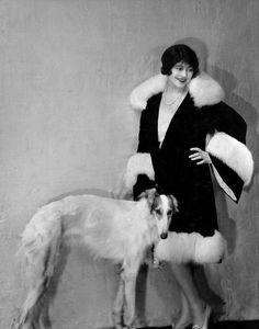 """Model wearing fashionable fur-trimmed coat with Russian Wolfhound dog at her side."""