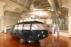 "Buckminster Fuller's 1934 Dymaxion ""2"" 4D Transport, courtesy of the National Automobile Museum (the Harrah Collection). Behind: Dymaxion House and photograph from the collections of the Henry Ford."