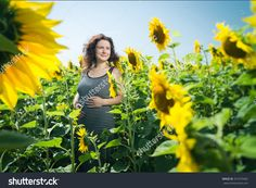 Girl stands in the field with sunflowers. Girl is pregnant. She is very happy. #shutterstock #family #lifestyle #happiness #woman #wheat #sunflowers #agriculture
