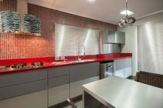 A arquiteta Graziella Aguiar não teve medo de usar cores fortes nessa cozinha de 12,5 m² localizada em um apartamento em Guarulhos (SP). No projeto com aura feminina, a neutralidade do aço inox é quebrada pelas pastilhas (Porto Design) e pela bancada, ambas vermelhas. A coifa Falmec ganhou um revestimento especialmente desenvolvido para o projeto, com estampa serigrafada