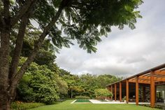 A casa possui paredes em pedra unidas por pórticos de madeira. A cobertura direciona a área social para o jardim e dá proporção horizontal à vista do vale.